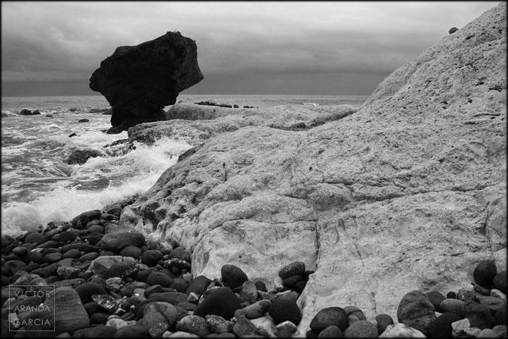 Fotografía en blanco y negro del mar chocando contra las rocas de la costa