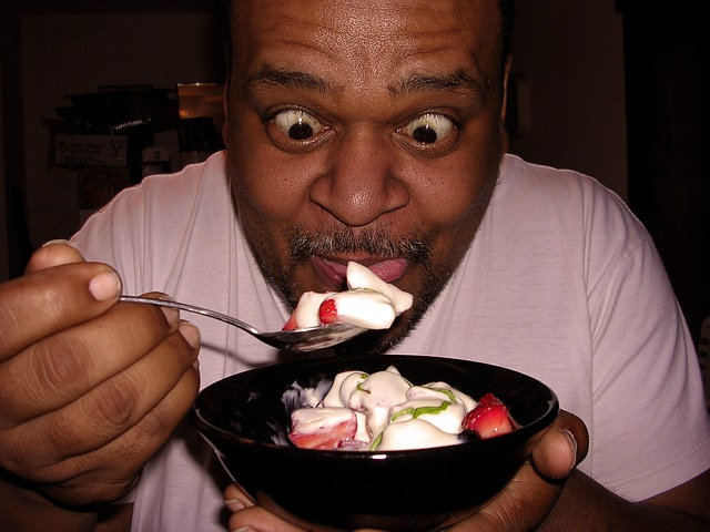 Man Hungrily Eating Yogurt and Fruit
