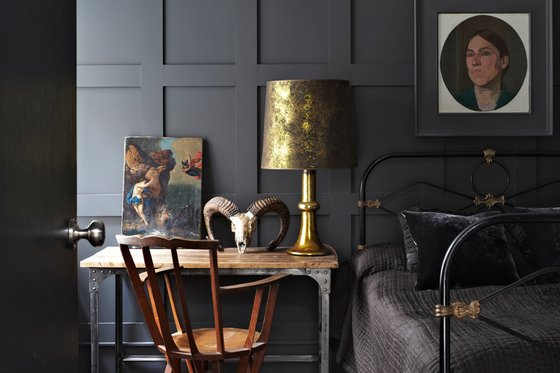 dormitorio pintado en gris oscuro con mesa de madera y hierro junto a silla de despacho chicanddeco