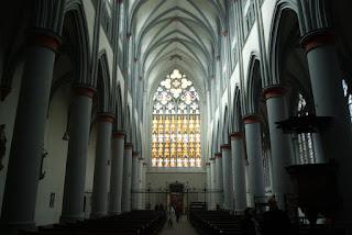 Auf diesem Bild sieht man das lichtdurchflutete Mittelschiff des Altenberger Doms. Die Säulen sind mit einem roten Kranz versehen.