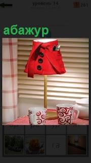 На столе стоит абажур красного цвета и рядом стоят две кружки с орнаментом