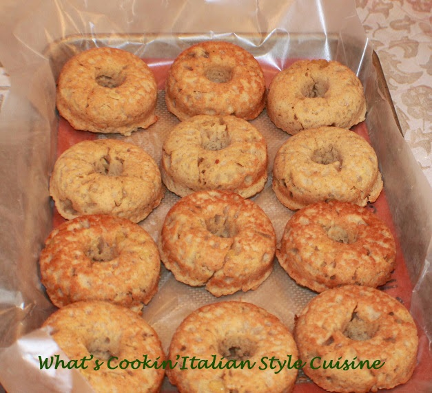 These are a baked donuts made with apples and cinnamon plain on wax paper cooling