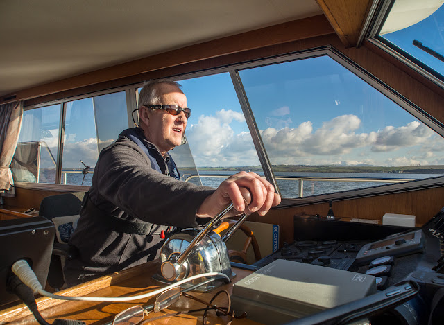 Photo of Phil at the helm of Ravensdale in the bright winter sunshine