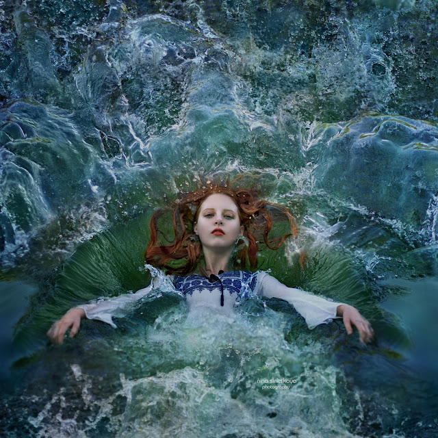 Young girl with red hair and pale skin is falling into colorful water