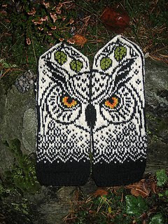 Knitted mitts with owl design in black and white and spots of color in the eyes.