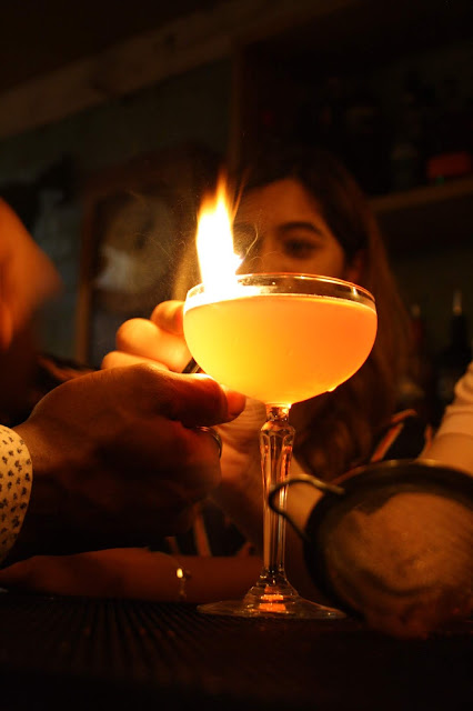 A Cosmopolitan cocktail in a glass, being set on fire on the Cosy Club bar