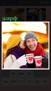 женщина с мужчиной пьют из кружек а на мужчине красный шарф