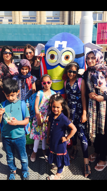 Women and children pictured posing with a Minion.