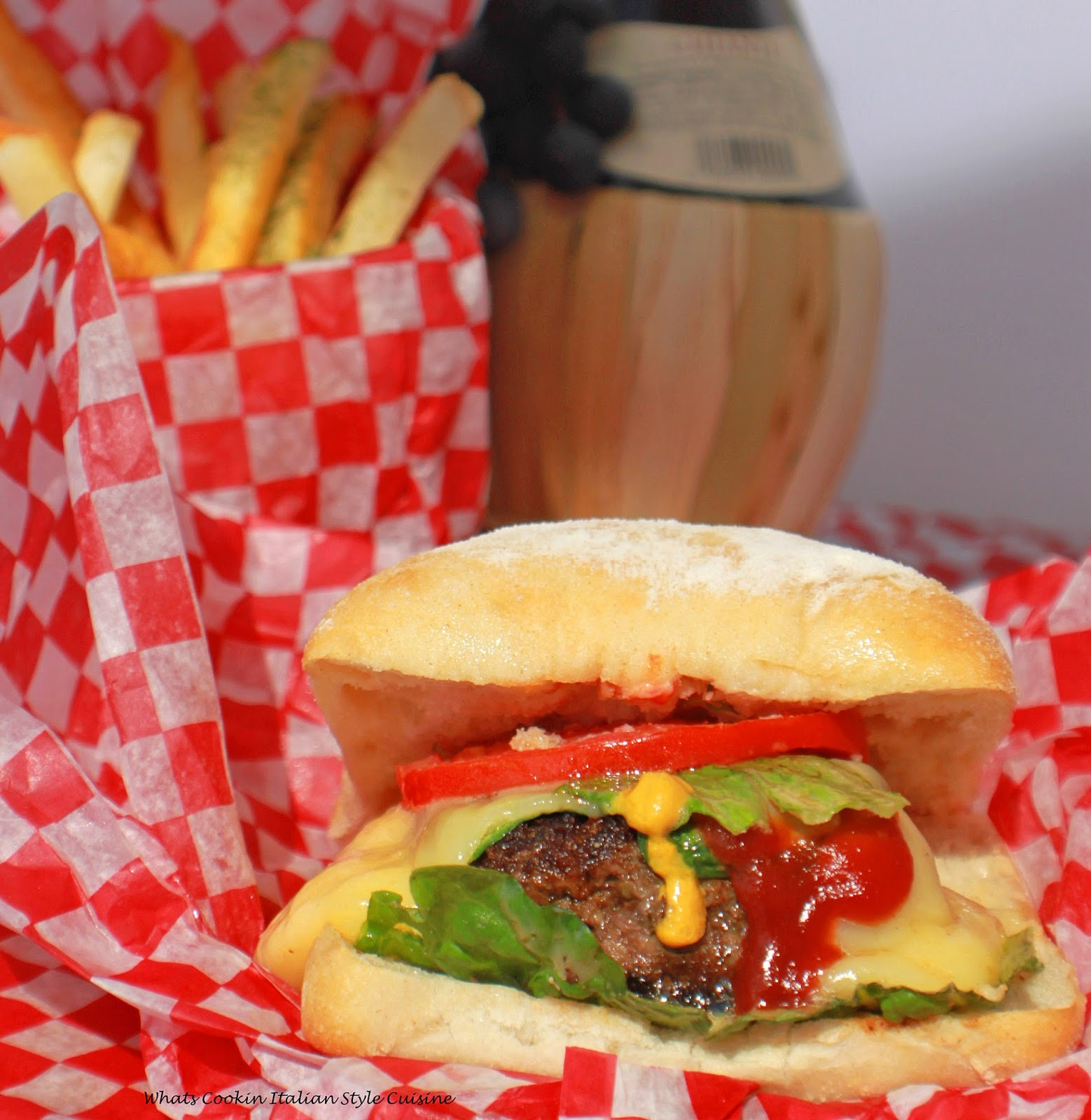 this is an Italian seasoned beef burger in a ciabatta bread roll pillow soft hamburger better than any fast food burger. This burger has lettuce tomato condiments, cheeses, and bursting with the best Italian flavors with french fries in a red and white checkerboard paper