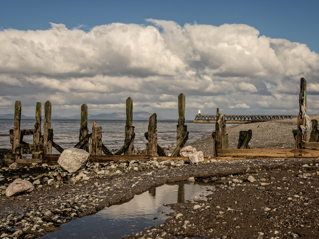 Photo of Maryport pier viewed through an old groyne on the beach