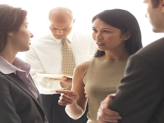 A lady conversing with colleagues at work makes her point