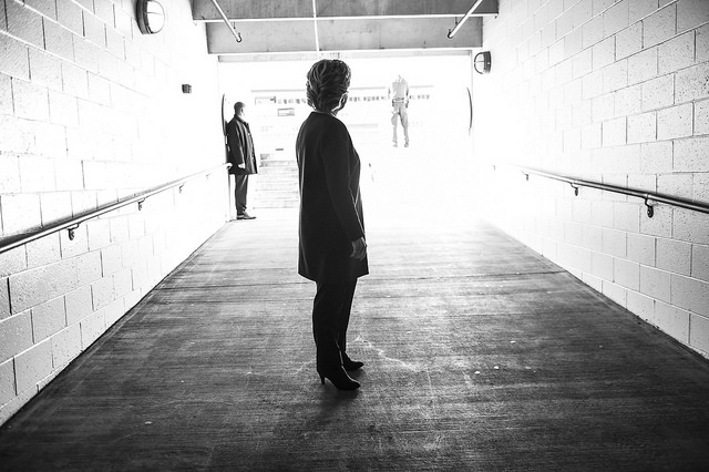 black and white image of Hillary Clinton standing in a long hallway, lookng toward the far end