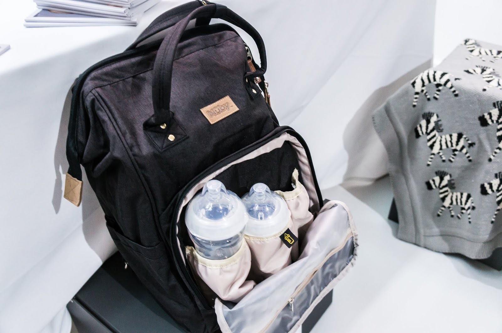black changing bag backpack containing baby bottles on display against white background at nuby big reveal event