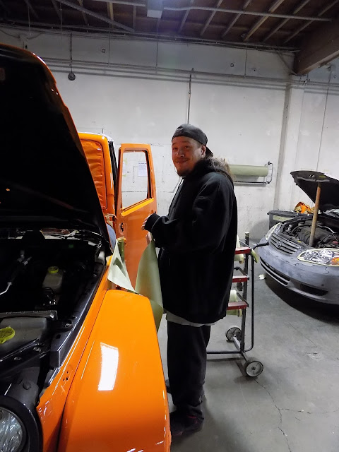 Paintline Technician masking a vehicle for paint.