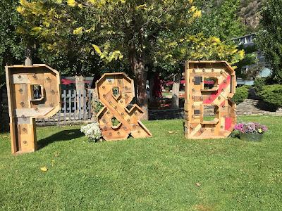 Letras gigantes luminosa hechas con madera reciclada, iniciales de los protagonistas
