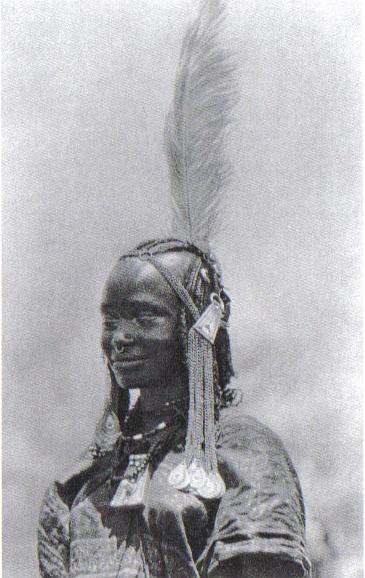 Woman with feather and other hair ornaments, Oulad-Hamid, Sudan. Photo: Bernatzik, first half of 20th century