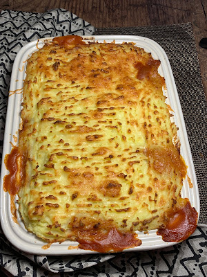 Cheesy Mashed Potato and Bean Bake in a casserole dish on a dark wood table