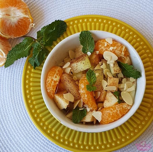 Salada de frutas com melão, maçã, tangerina, lascas de amêndoas, folhas de hortelã e canela em pó polvilhada por cima.