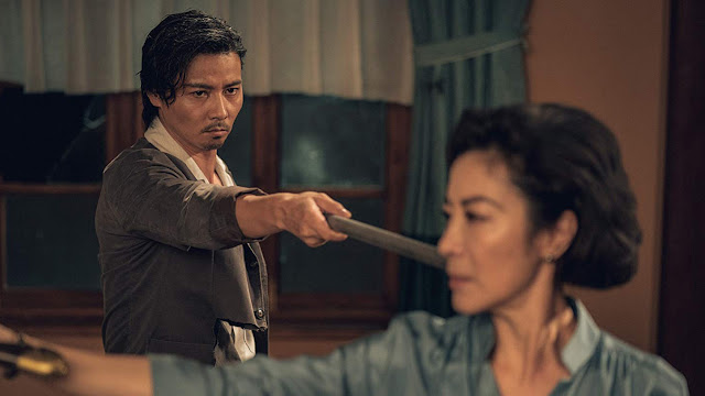 man points a pipe at michelle yeoh