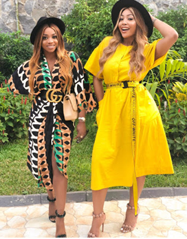 Kika good hair in a black patterned dress with Chioma in Yellow flowing dress. Both have hats on