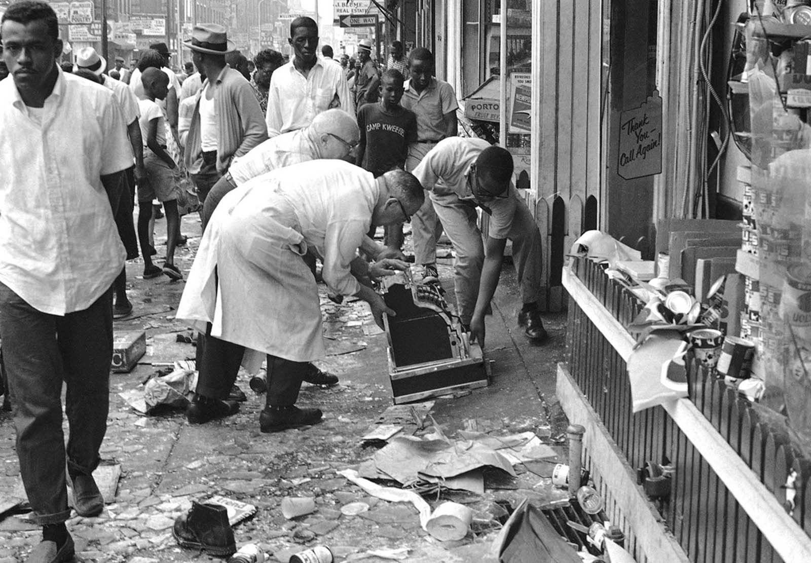 Workmen move a cash register off the sidewalk in front of smashed store, wrecked during wild night of looting and rioting in North Philadelphia, on August 29, 1964.