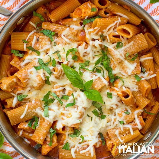 close up image of skillet meal with Italian chicken on bed of penne pasta