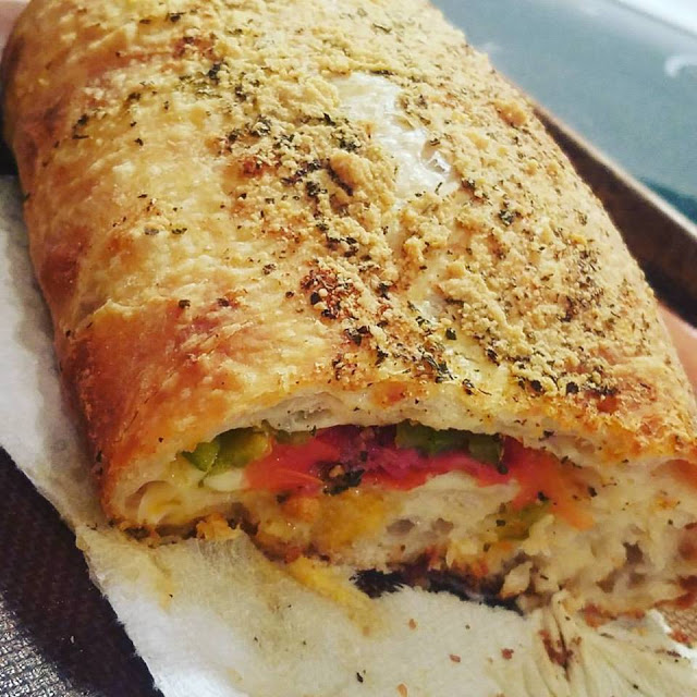 pizza dough stuffed with sausage, cheese, olives, pepperoni, tomoatoes, peppers, in homemade pizza dough called stromboli