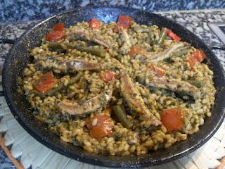 Paellera de arroz con boquerones y verduras.