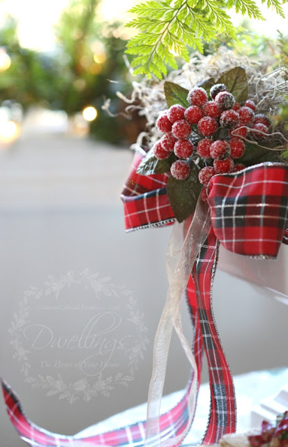 Red berries and plaid ribbon add a Christmas touch to an ironstone compote filled with a rabbits foot fern