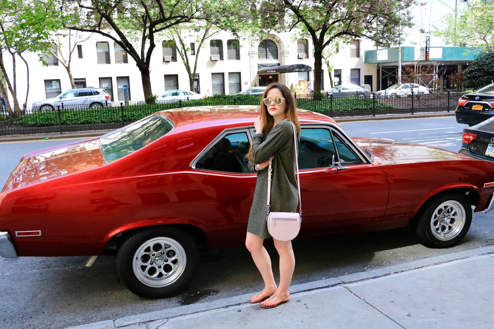 Fashion blogger Kathleen Harper in front of a red car
