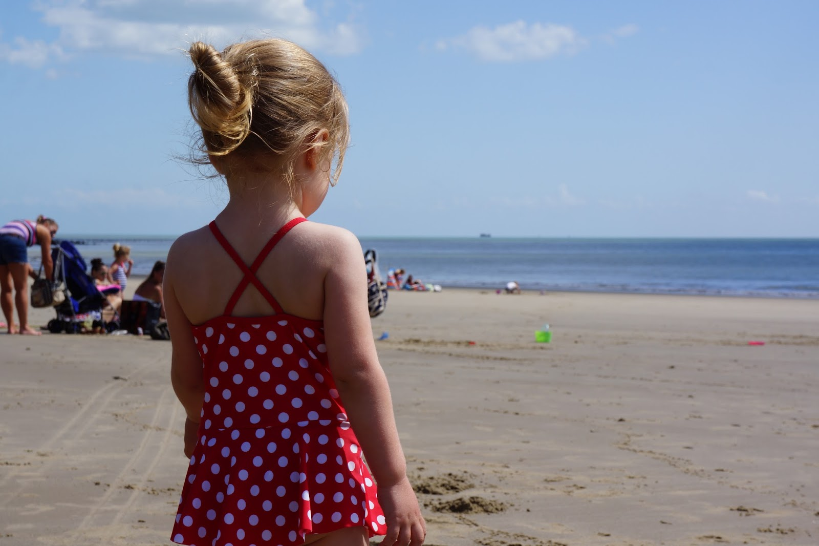 toddler looking towards the sea in a swimsuit