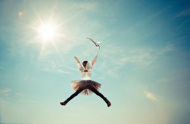 girl in tutu dress flying sun