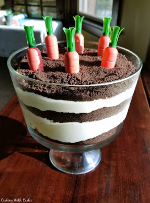 trifle bowl of dirt pudding with pudding and cookie crumbs with carrots on top