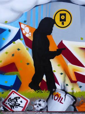 """Wandbild mit Müll und """"Stop War""""-Schild, inmitten dessen ein schwarzer Pistolenmann"""