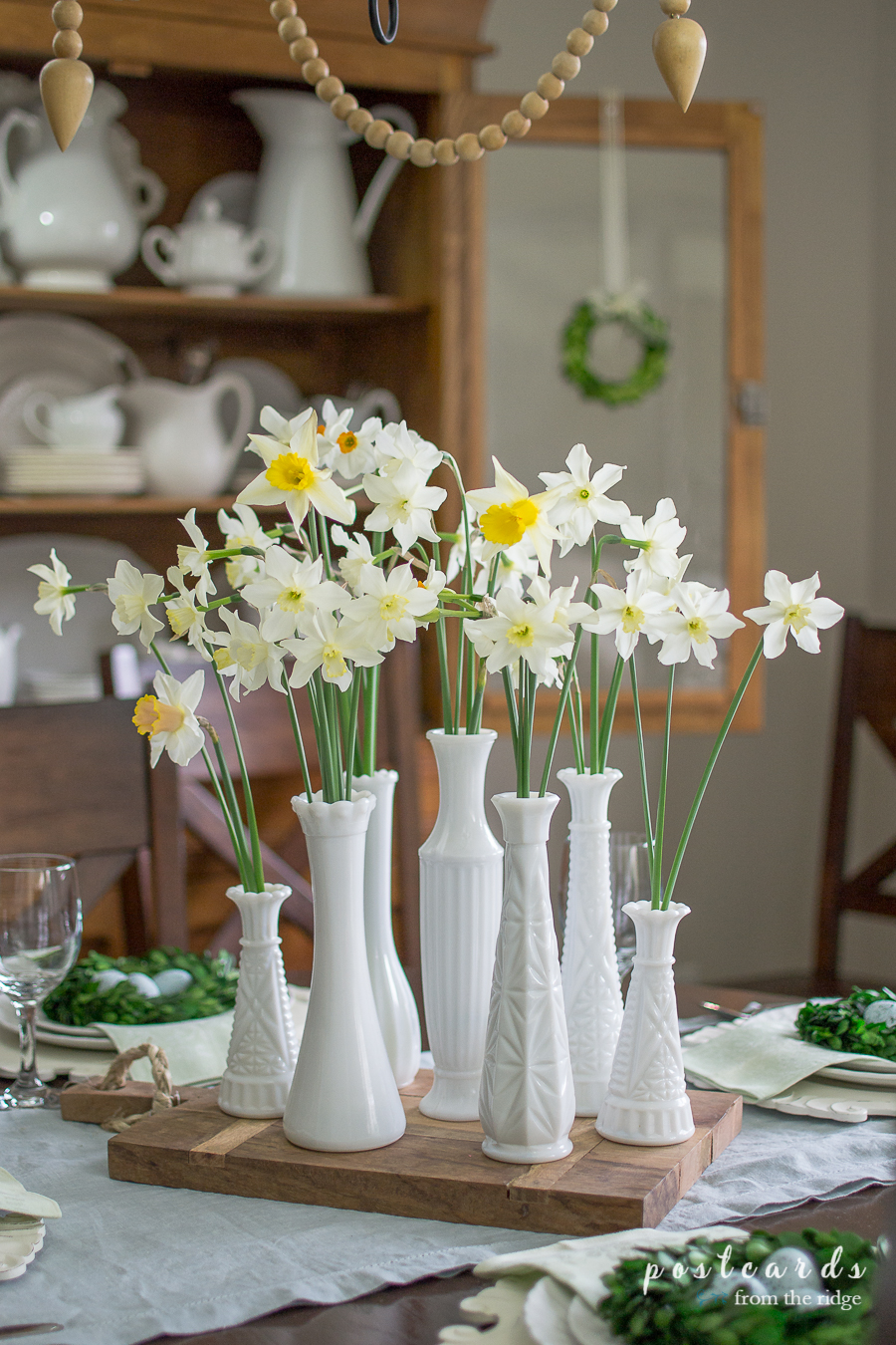 flowers in white milk glass vases grouped together as a centerpiece