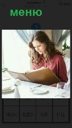 за столом девушка изучает открытое меню