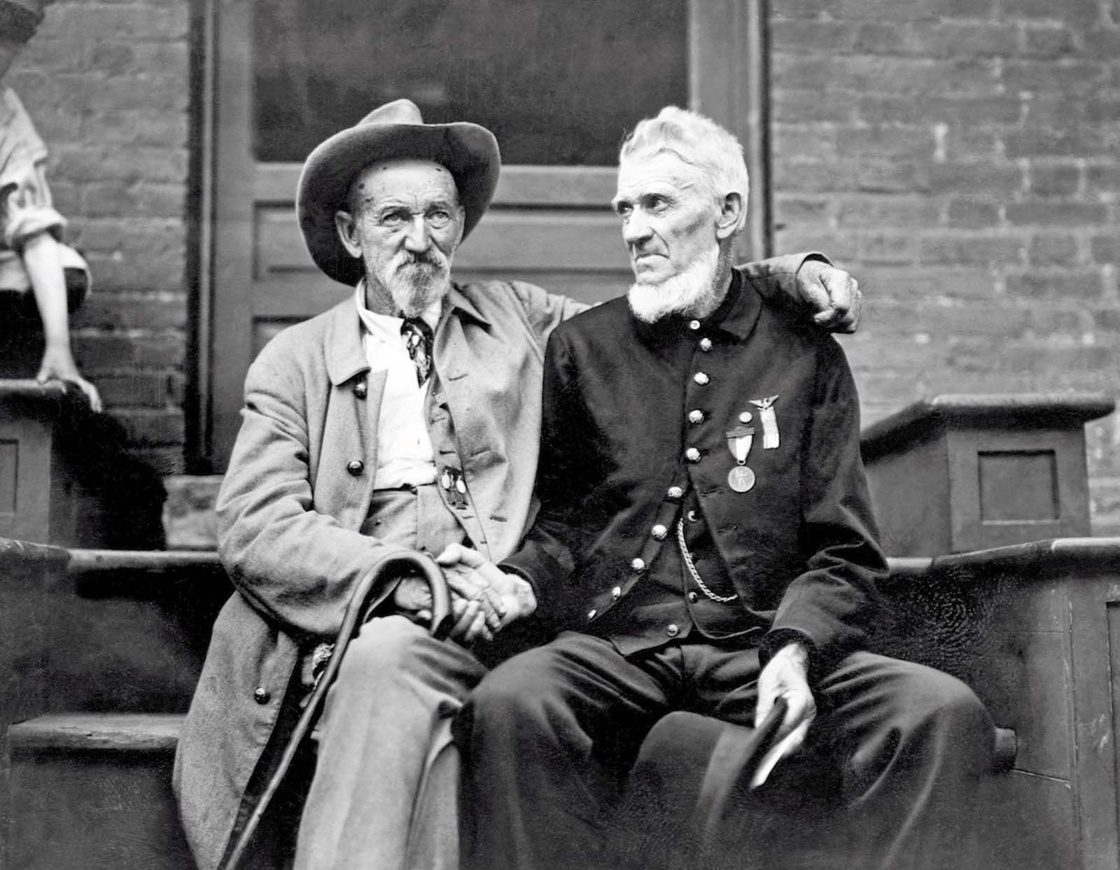 A veteran of the Union Army shakes hands with a Confederate veteran at the Gettysburg celebration, in Pennsylvania. 1913.