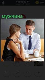 сидят мужчина и женщина за столом, на котором стоят чашки