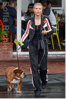 ソフィア・リッチー(Sofia Richie)は、マージュ(Maje)のライダースジャケット、ジバンシー(Givenchy)のスウェットパンツ、アレキサンダーワン(Alexander Wang)のバッグを着用。