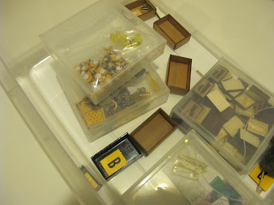 Plastic tub containing a number of miniature wooden crates and packages of miniature items.