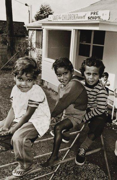 Vintage foto australia: tres niños juegan sobre un varandal de fierro en el jardin de niños local.