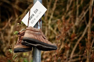 Ein paar braune Wanderschuhe hängen mit Kaputter und heruntergeklapper Sohle an einem kleinen Schild.