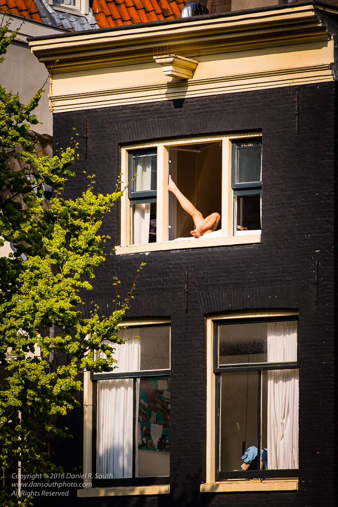 a photo of bare legs in a window in amsterdam
