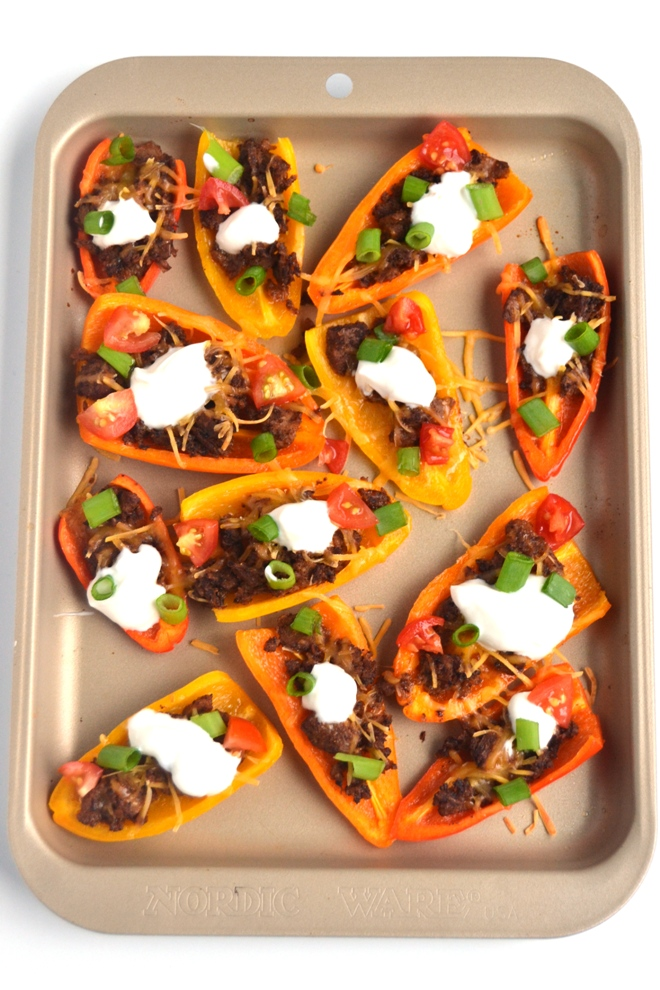 Mini Bell Pepper Nachos are a healthier vegetarian version of your favorite appetizer, ready in just 15 minutes and are topped with cheddar cheese, tomatoes, green onions and more! www.nutritionistreviews.com