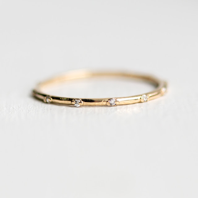 Slim round stackable band with tiny white diamonds set in 14k yellow gold