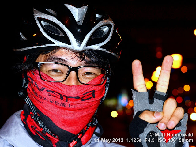 people, street portrait, headshot, face, eyes, Taiwan, Taipei, face bandana, cyclist, bicycle helmet, V sign, eye contact
