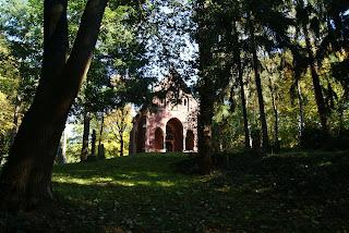 Eine, aus Ziegelsteinen erbaute Kapelle steht auf einer Anhöhe etwas von Bäumen verdeckt.