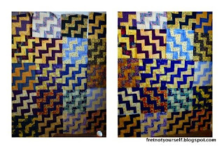 Purple and gold fabrics alternate to make the rails in this quilt design.