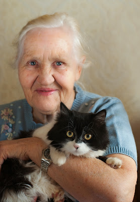 An elderly woman holding her black and white cat