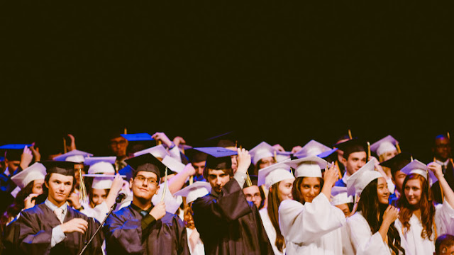 A group of smiling, mostly white graduates adjusting their tassels at the close of the ceremony.